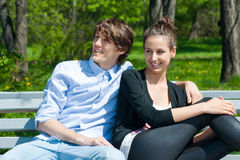Couple sitting together on park bench Stock Photos