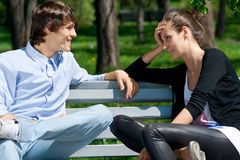Couple sitting together on park bench Stock Photo