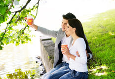Couple sitting together on the riverside and drinking coffee Royalty Free Stock Image