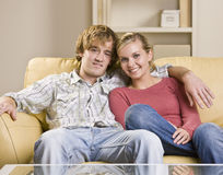 Couple sitting together on sofa Royalty Free Stock Images