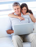 Couple sitting together on a sofa and working Stock Photo