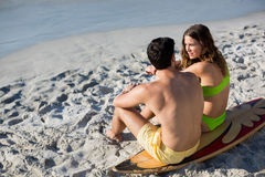 Couple sitting together on surfboard at beach Royalty Free Stock Photography