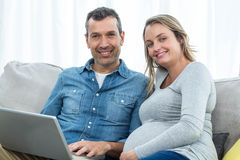 Couple sitting together and using laptop Stock Photo