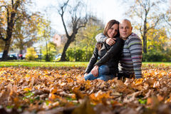 Couple Sitting Together In The Woods During Autumn Stock Photo