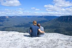 Couple sitting on top of mountain. Hetero couple enjoying scenic view of blue mountains near Sydney, New South Wales, Australia, while sitting on top of rock Royalty Free Stock Photo