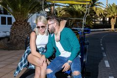 Couple sitting at touristic cart. Cheerful couple sitting and embracing at touristic cart on resort Stock Photography