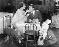 Couple sitting on a toy table having tea together Stock Images