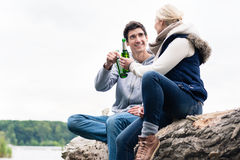 Couple sitting on tree stump at the riverside drinking beer Stock Photography