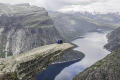 Couple sitting on trolltunga troll`s tongue rock , Norway royalty free stock image
