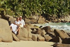 Couple sitting   at tropical beach. Happy elderly couple sitting   at tropical beach Stock Images