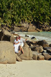 Couple sitting   at tropical beach. Happy elderly couple sitting   at tropical beach Stock Photo