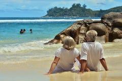 Couple sitting  on  tropical beach. Happy elderly couple sitting  on  tropical beach Stock Images