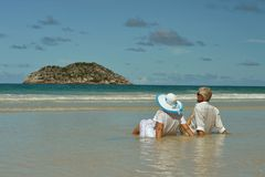 Couple sitting  on  tropical beach. Happy elderly couple sitting  on  tropical beach Stock Photo