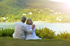Couple sitting  on  tropical beach. Happy elderly couple sitting  on  tropical beach. Back view Royalty Free Stock Images