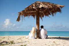 Couple sitting under palm umbrella Royalty Free Stock Photo
