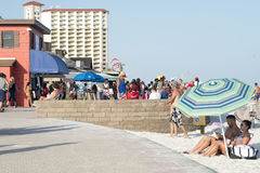 Couple sitting under an umbrella on a beach boardwalk. White american couple sits under an umbrella on a beach boardwalk while crowds gather nearby Royalty Free Stock Photo
