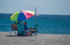 A couple sitting under an umbrella on the sand on a beach in Florida Stock Image
