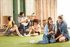 Couple sitting and using smartphone while their friends playing guitar behind Royalty Free Stock Image