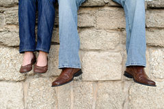Couple sitting on wall feet only. A couple sitting on an old wall dangling their feet. Their faces are not shown royalty free stock photography