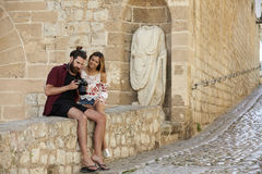 Couple sitting on wall looking at photos on a camera, Ibiza Royalty Free Stock Photos