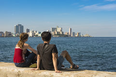 Couple sitting on wall at Malecon Havana Royalty Free Stock Photos