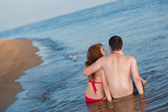 Couple sitting in water Royalty Free Stock Photography