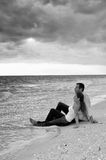 Couple sitting in water at the beachin black and w. Attractive young couple sitting in the water fully dressed at the beach with big cloud bank overhead looking Royalty Free Stock Photo