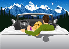 Couple sitting in white convertible car hugging and looking at the mountains under the night sky Stock Photo