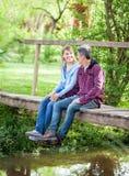 Couple Sitting On Wooden Bridge Stock Photos