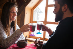 Couple sitting in wooden cottage and drinking mulled vine Royalty Free Stock Images