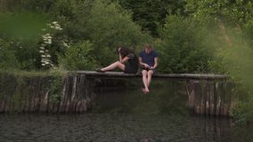 Couple sitting on a wooden pontoon on a river in summertime. Husband using a digital tablet and wife is angry and upset stock video