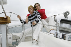 Couple Sitting On Yacht By Helm Royalty Free Stock Image