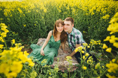 Couple sitting among yellow flowers in meadow embracing, touching by face each other. Girlfriend wearing green dress, husband in c Royalty Free Stock Photography