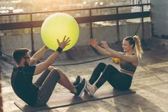 Couple doing crunches with a pilates ball royalty free stock photos