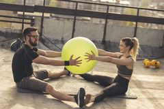 Couple exercising with a pilates ball. Couple sitting on a yoga mat on a building rooftop terrace, exercising with a pilates ball stock photo