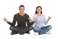Couple sitting in yoga position Stock Photos