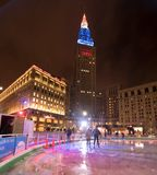 Ice skating in Public Square in front of Terminal Tower. A couple skate in the park in front of the red, white and blued tower at night Stock Image