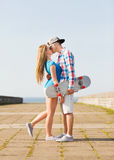 Couple with skateboard kissing outdoors Stock Images