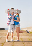 Couple with skateboard kissing outdoors Royalty Free Stock Photo