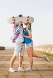 Couple with skateboard kissing outdoors Stock Photography