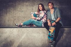 Couple with skateboard outdoors Stock Photos