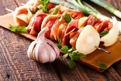 Couple of skewers with vegetable and herbs on wooden board Stock Images