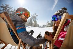 Couple resting in sunbed and drinking tea. Couple with ski goggles resting in sunbed and drinking tea Royalty Free Stock Photo