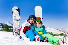 Couple in ski mask sitting on snow Royalty Free Stock Photo