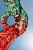 Couple in ski suits with sunglasses holding hands on blue sky ba Stock Images
