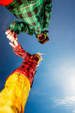 Couple in ski suits with sunglasses holding hands on blue sky ba Royalty Free Stock Photo