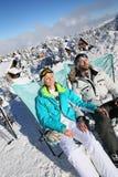 Couple of skiers enjoying the sun on the slopes Royalty Free Stock Photos