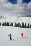 A couple of skiers following a track in the snow stock images