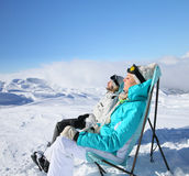 Couple of skiers on long chairs taking sun Royalty Free Stock Images