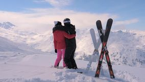 Couple Skiers In Love Kisses and Hugs on the Top of the Mountain. A happy young couple in love stands on the top, kissing, hugging and enjoying a beautiful stock footage